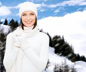 winter holidays, vacation, people and happiness concept - woman in hat, muffler and gloves
