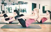 fitness, sport, training, gym and lifestyle concept - group of smiling women exercising on mats in t