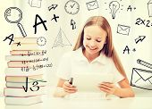 education, school, technology and internet concept - little student girl with tablet pc and books at