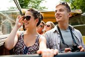 friendship, travel, vacation, summer and people concept - smiling couple with camera traveling by to