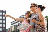 travel, tourism, vacation, summer and people concept - smiling friends with map and city guide point