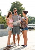 travel, tourism, vacation, summer and people concept - smiling friends with map and city guide outdo