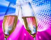 Champagne Flutes With Golden Bubbles Make Cheers On Sparkling Blue And Violet Disco Ball Background