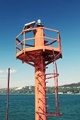 Small Red Lighthouse Pole On The Coast Of Black Sea