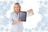 Happy blonde pointing to her tablet pc screen against snowflake frame
