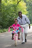 Smiling African American Man Helping Little Girl Biking Outdoor, grandpa and grand daughter