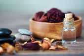 Dry roses in bowl, spa stones and aromatic oil
