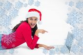 Beautiful festive woman pointing to laptop against snowflake frame