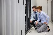 picture of kneeling  - Team of technicians kneeling and looking at servers in large data center - JPG