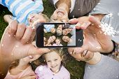 Hand holding smartphone showing extended family lying in circle at park