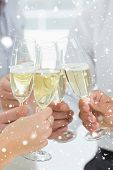 Hands toasting with champagne against snow falling