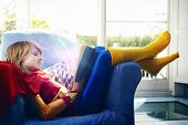 Little boy dressed as a super hero reading a book