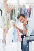 Bored man with shopping bags while woman by clothes rack against snow falling