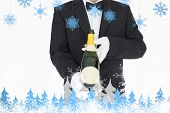 Waiter holding champagne bottle against snowflakes and fir trees