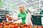 Shopping. Woman choosing bio food fruit tomato in vegetable store or supermarket