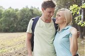 Romantic young couple looking at each other while hiking in forest