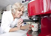Senior woman dispensing coffee from machine at kitchen counter