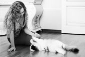 Beautiful woman playing with a cat on the floor