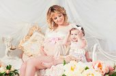 Pregnant Mother And Cute Little Daughter In Cozy Room With Flowers.