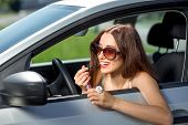 An Attractive Young Woman Applying Lipstick In The Rear View Mirror While Driving