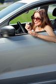 Young woman drawing eyelashes in the rear view mirror while driving
