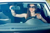 Young Woman Drinking Coffee While Driving Her Car