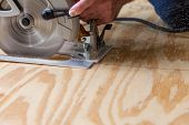 picture of sawing  - Man using a circular saw to cut plywood - JPG