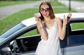 Young Woman Showing A Key And License In Front Of The Car. Girl Pass Successfully Driving Exam.