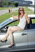 Young Woman Holding Keys To New Car Smiling At Camera And Sitting On The Car Door