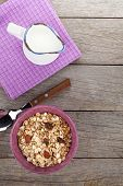 Healthy breakfast with muesli and milk. View from above on wooden table with copy space