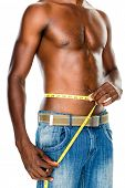 Mid section of a fit shirtless man measuring waist over white background