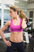 Serious fit young woman lifting kettle bell in the gym