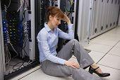 Stressed technician sitting on floor beside open server in large data center