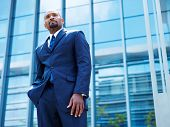 confident african businessman in front of glass building