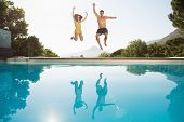 Full length of a cheerful young couple jumping into swimming pool
