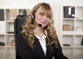 foto of telemarketing  - Friendly businesswoman wearing a headset looking at the camera with a lovely smile conceptual of a call centre client services reception or telemarketing - JPG