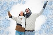 Attractive young couple in warm clothes with arms up against snowflake frame
