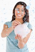 Lovely woman inserting a coin in a piggy bank against snow falling