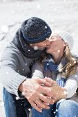 Attractive couple kissing on the beach in warm clothing against snow falling