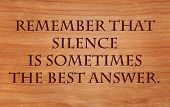 Remember that silence is sometimes the best answer - an old saying on wooden red oak background