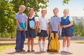 Several kids in school uniform outside