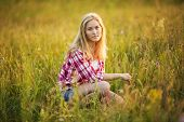 Beautiful Girl Is Sitting In The Grass