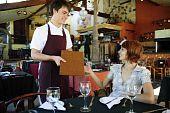 Waiter Giving Menu To Costumer At The Restaurant