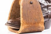 stock photo of caribou  - Vintage Caribou Hide Cowboy Boot in antique homemade wooden saddle stirrup against white background - JPG