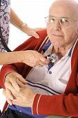 stock photo of hospice  - shot of a nurse checking elderly mans heart - JPG