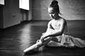 Adorable ballerina tying up her shoes