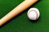 Close-up of baseball ball and bat on artificial green grass