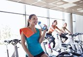 sport, fitness, lifestyle, equipment and people concept - group of women with water bottle riding on exercise bike in gym