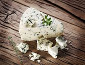 Slices of Danish Blue cheese on an old wooden table.