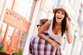 stock photo of cheers  - Rear view of young cheerful man carrying his beautiful girlfriend on shoulder while walking by the street - JPG